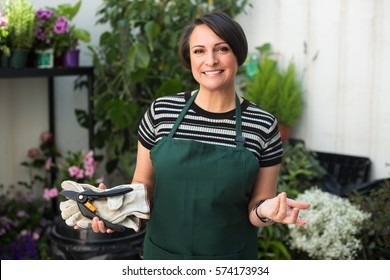 Friendly smiling woman florist in apron holding horticultural tools in gardening store