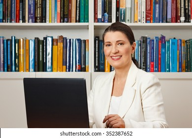 Friendly smiling woman in front of a computer in a library, consultant, counselor, adviser, customer service, online helpline
