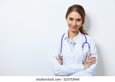 Friendly smiling young female doctor, standing near wall