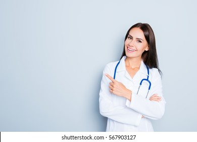 Friendly smiling young female doctor pointing with finger.