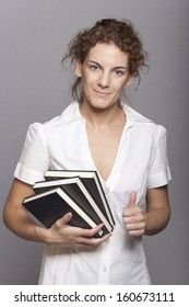 Friendly smiling young woman holding books