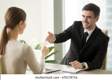 Friendly successful businessman giving visiting business card to businesswoman at office during first meeting with interested client, offering pasteboard, personal information, call me, contact us