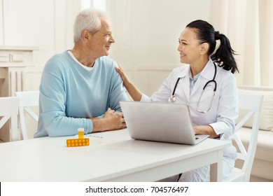 Friendly sympathetic doctor putting her hand on the patients shoulder