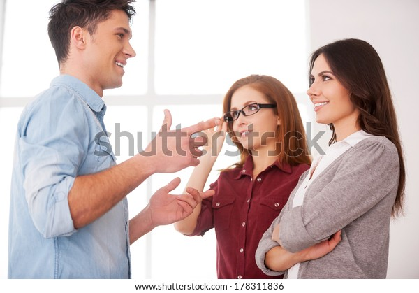 Friendly talk. Discussing a good condition contract. Two beautiful young women discussing document while two men communicating on background