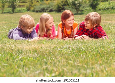 Friendly talk. Upbeat children smiling and talking while lying on the grass together.