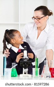 friendly teacher talking to elementary student in science class