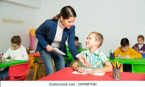 Friendly teacher woman helping boy during lesson in schoolroom