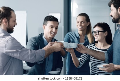 Friendly team. Cheerful smiling young colleagues having a break in the office while drinking coffee and expressing positivity