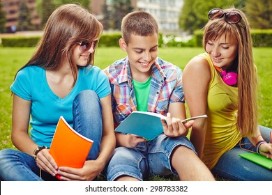 Friendly teenagers with exercise-books carrying college tasks on green lawn