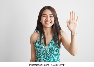 Friendly Thai Asian girl with a kind smile shows a welcome gesture with the palm of her hand, says hello on a white studio background