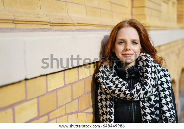 Friendly thoughtful young redhead woman in a trendy scarf leaning against an exterior wall gazing at the camera with copy space