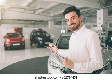 friendly vehicle salesman presenting new cars at showroom. Photo of young male consultant showing new car in auto show. Concept for car rental
