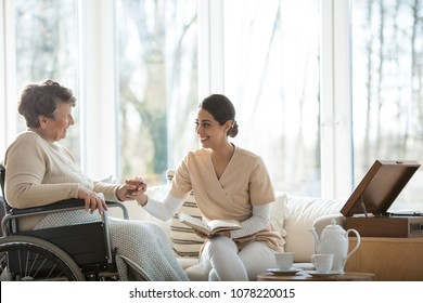 Friendly volunteer reading a book to a disabled senior woman in a hospice