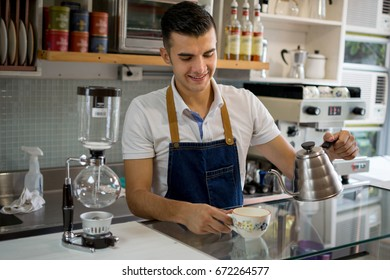 Friendly waiter serving a cup of tea on the counter and looking very happy
