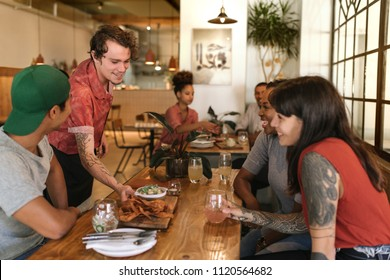 Friendly waiter serving delicious freshly made tapas to a group of laughing customers sitting at a table in a bistro