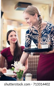 friendly waitress serving clients with coffee in a stylish restaurant