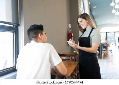 Friendly waitress taking an order from a customer in a coffee and bakery shop