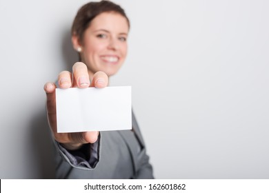 Friendly woman holding a business card and smiling