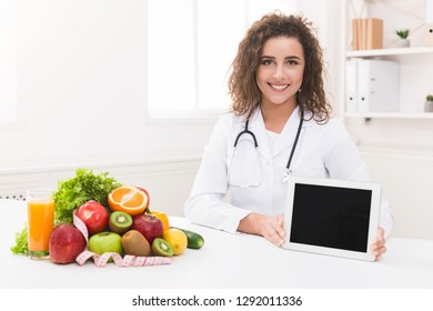 Friendly woman nutritionist recommend new dietary application, showing blank digital tablet, copy space