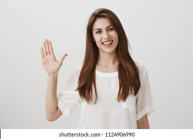 Friendly woman says hi to new neighbours. Portrait of charming young emotive woman waving with raised hand, greeting or welcoming close friend, smiling broadly at camera, standing over gray wall