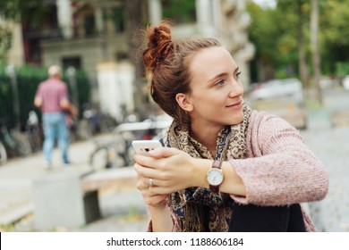 friendly woman sitting on a bench in the city center holding her smart phone