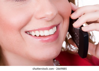 Friendly woman smiling with cell phone. Isolated on white.