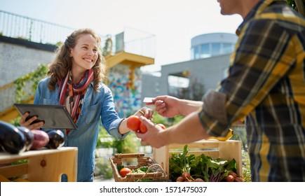 Friendly woman tending an organic vegetable stall at a farmer's