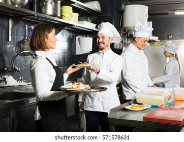 friendly woman waiter collecting freshly prepared dishes from restaurantâ??s kitchen