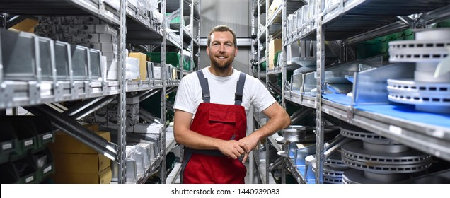 friendly worker in a warehouse and trade for car spare parts of a car repair shop
