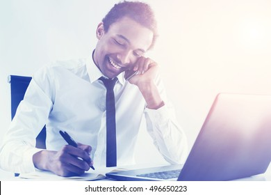 Friendly young african american businessman having phone conversation while working at office desk on light background.  Toned image