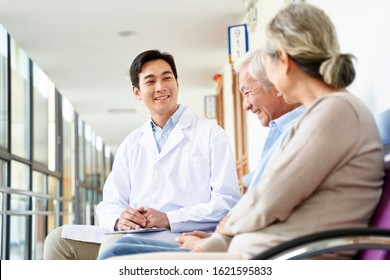 friendly young asian doctor talking to old couple in hospital hallway