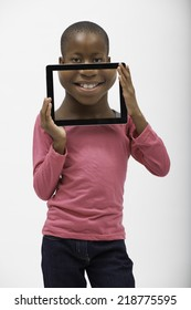 Friendly young black girl with a pink top and black pants holding a tablet with magnified image of her mouth in front of her face