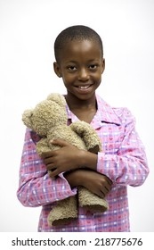 Friendly young black girl wearing pink pajamas holding teddy bear