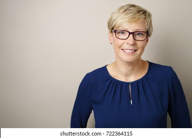 Friendly young blond woman wearing glasses posing over a white studio background with copy space