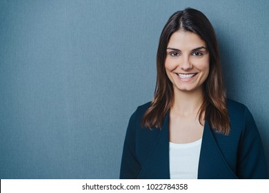 Friendly young businesswoman with a beaming smile over a grey background with copy space