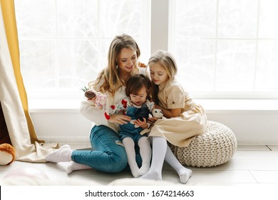 Friendly young family having good time together in a bright room. Little baby girl jumping in the bed. Lay and on the sofa hugging a bunny