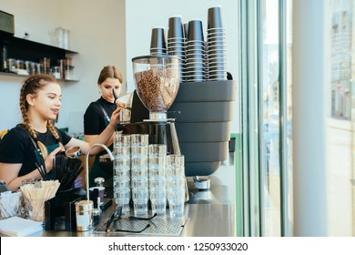 Friendly young female barista in apron with two braids preparing coffee working order. Small business owner and person at work concept.