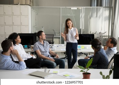 Friendly young female coach teacher, mentor or worker speaking at diverse corporate group meeting talking to colleagues at training teaching intern explaining new idea at sales team office briefing
