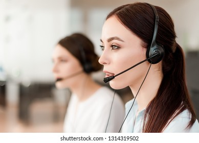 Friendly young female technical support dispatcher with a headset working in a call center on a hotline, talking on the phone. Portrait of an attractive customer care representative