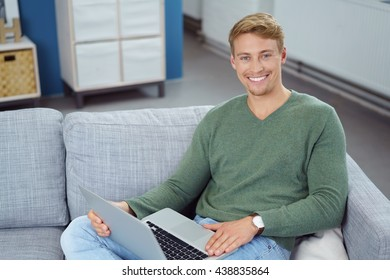 Friendly young man with a lovely beaming smile relaxing on a sofa at home with a laptop computer, high angle view