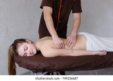 Friendly young man masseur concentrated and gently makes useful medical procedure and drives hands along back to nice girl who came to reception and lies on couch to half covered by terry towel in