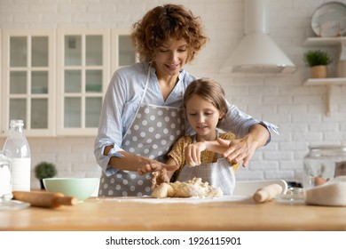 Friendly young mother little daughter cook dessert bakery at modern kitchen knead dough with hands enjoy preparing cookies bread spend time together. Small girl learn to bake with help of caring mom