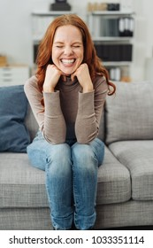 Friendly young redhead woman sitting on a sofa at home beaming at the camera with her eyes closed