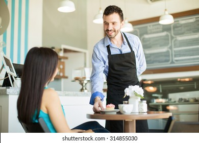 Friendly young waiter serving a cupcake and some coffee to one of his customers in a cake shop