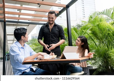 Friendly young waiter talking with the clients after serving them coffee and food at a table outdoors in a trendy restaurant downtown