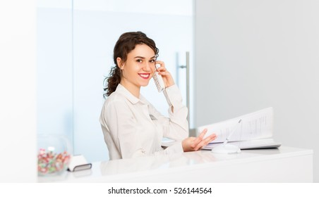 friendly young woman behind the reception desk administrator