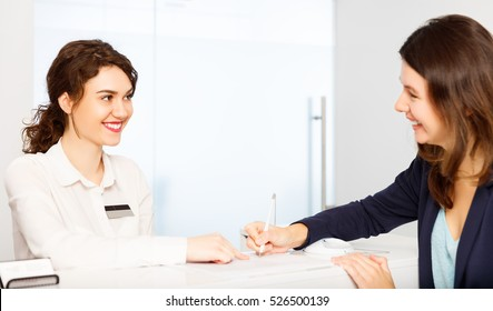 friendly young woman behind the reception desk administrator with customer visitor
