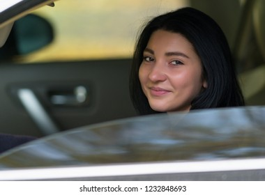 Friendly young woman driver smiling at the camera as she looks out of the side window of the car in a close up portrait