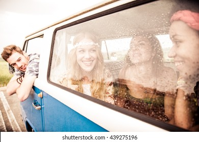 Friends in a 70's styled minivan repairing from summer rain, girls are talking and having fun