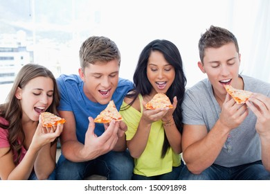 Friends about to take the first bite of their pizza slices